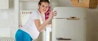 Беременная девушка заглядывает в холодильник